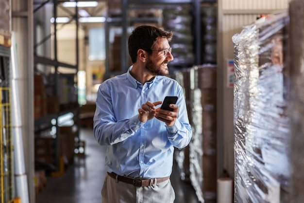 Young smiling attractive bearded businessman standing in warehouse and using smart phone.