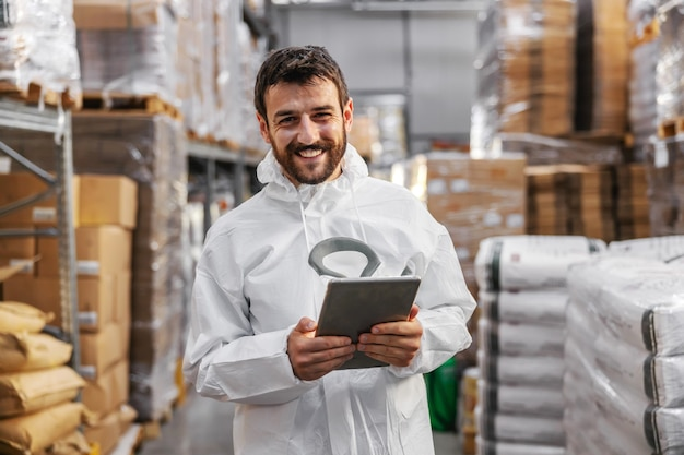 Young smiling attractive bearded supervisor in protective uniform holding tablet and checking on goods salary while standing in food factory. corona virus outbreak concept.