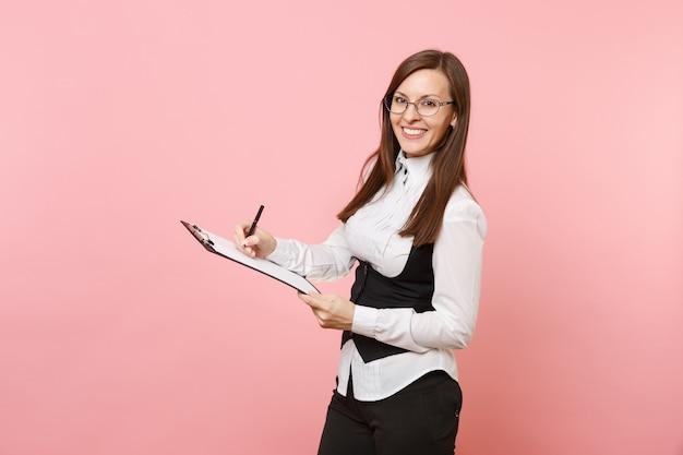 분홍색 배경에 격리된 종이 문서가 있는 클립보드 태블릿에 안경을 쓴 젊은 미소의 매력적인 비즈니스 여성. 여사장님. 성취 경력 부입니다. 광고 공간을 복사합니다.
