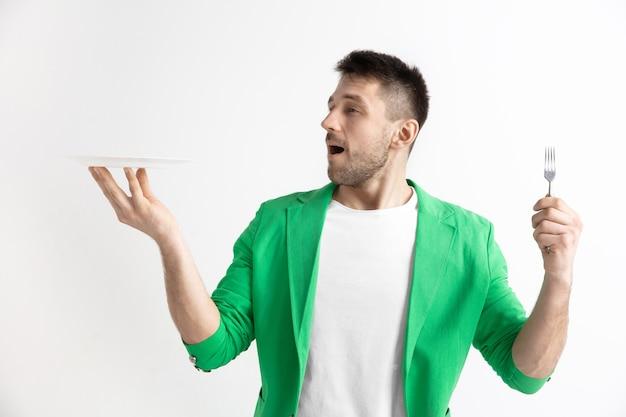 Молодой улыбающийся привлекательный кавказский парень, держащий пустое блюдо и вилку, изолированные на сером фоне. скопируйте место и сделайте макет. пустой шаблон фона.