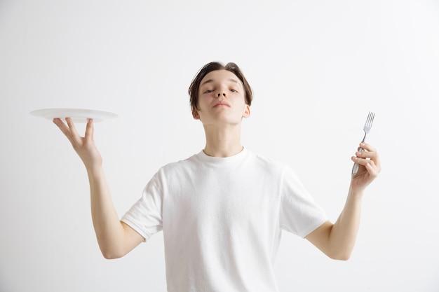 Giovane ragazzo caucasico attraente sorridente che tiene piatto vuoto e forchetta isolato su sfondo grigio. copiare lo spazio e simulare. sfondo modello vuoto.