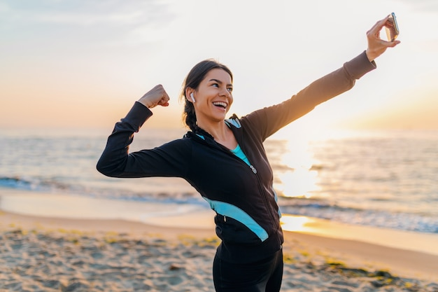 Young smiling attractive slim woman doing sport exercises on morning sunrise beach in sports wear, healthy lifestyle, listening to music on earphones, making selfie photo on phone looking strong