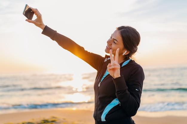 スポーツウェア、健康的なライフスタイル、イヤホンで音楽を聴き、ポジティブな気分で電話で自分撮り写真を作る朝の日の出ビーチでスポーツエクササイズをしている若い笑顔の魅力的なスリムな女性