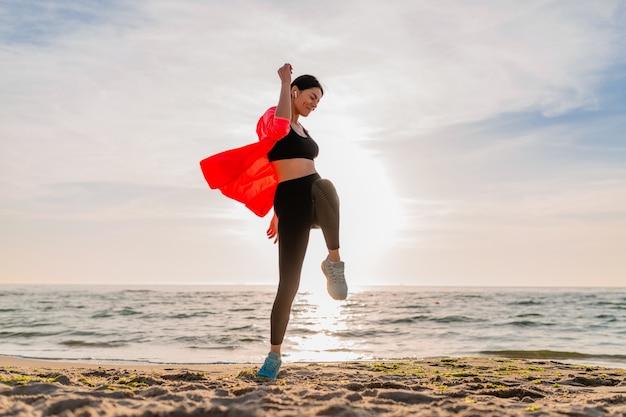 Молодая улыбающаяся привлекательная стройная женщина занимается спортом в утреннем восходе солнца, прыгает на морском пляже в спортивной одежде, здоровом образе жизни, слушает музыку в наушниках, в розовой куртке-ветровке, веселится