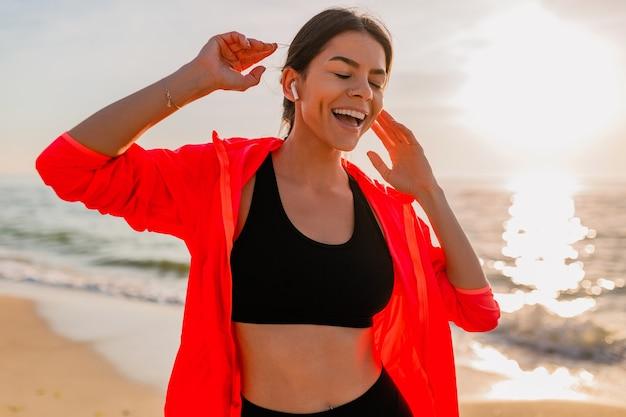 Giovane donna sottile attraente sorridente che fa sport all'alba mattutina ballando sulla spiaggia del mare in abbigliamento sportivo, stile di vita sano, ascoltando musica con gli auricolari, indossando giacca a vento rosa, divertendosi