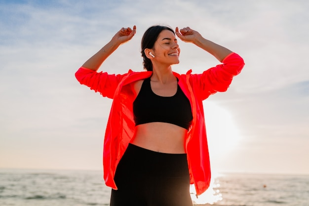 Young smiling attractive slim woman doing sports in morning sunrise dancing on sea beach in sports wear, healthy lifestyle, listening to music on earphones, wearing pink windbreaker jacket, having fun