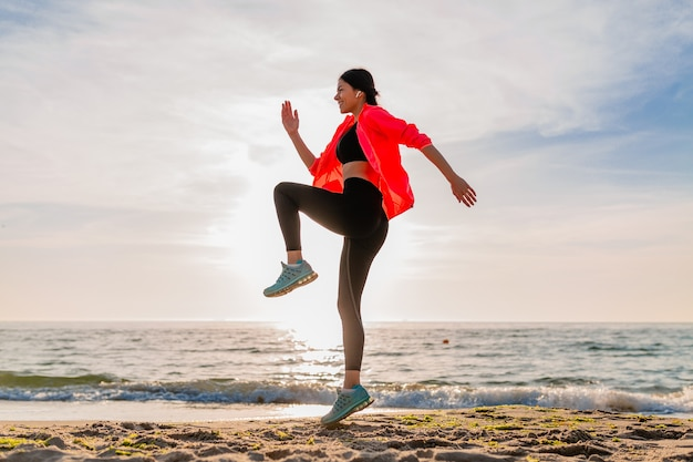 Young smiling attractive slim woman doing sports in morning sunrise jumping on sea beach in sports wear, healthy lifestyle, listening to music on earphones, wearing pink windbreaker jacket, having fun