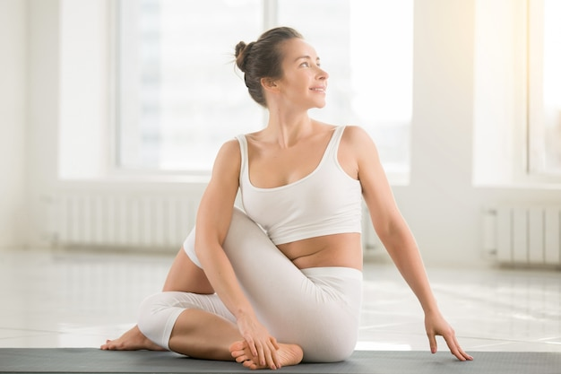 Young smiling attractive woman in ardha matsyendrasana pose, whi