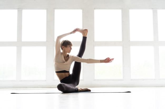 ヨガを練習している若い笑顔の魅力的な女性