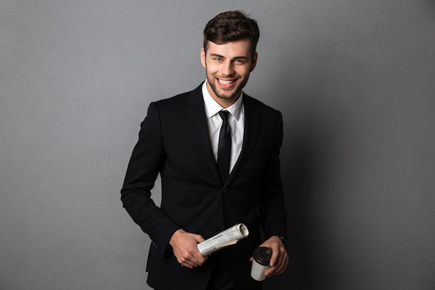 Young smiling bearded man in formalwear holding newspaper and cup of coffee,