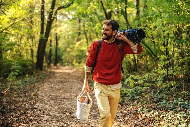 Young smiling bearded man walking in nature, having backpack on backs and holding picnic equipment.