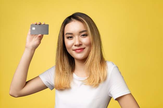 Young smiling beautiful asian woman presenting credit card in hand showing trust