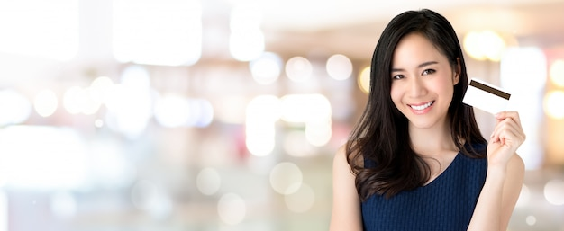Young smiling beautiful asian woman presenting credit card in hand