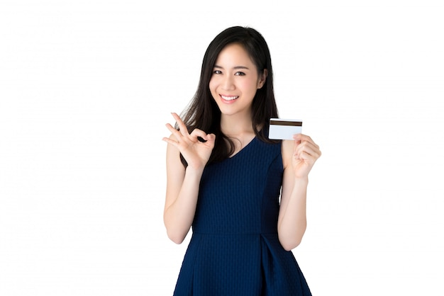 Young smiling beautiful asian woman showing credit card with okey gesture
