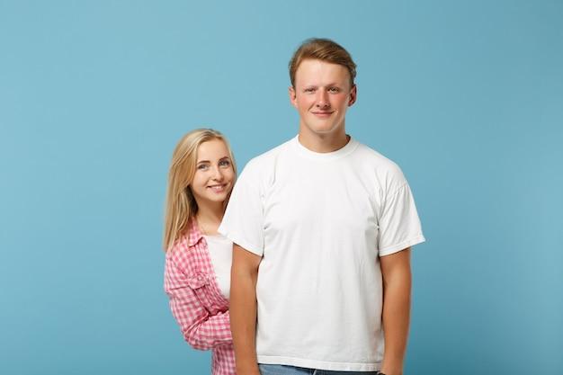 白いピンクの空の空白のtシャツのポーズで若い笑顔の美しいカップル2人の友人の男と女