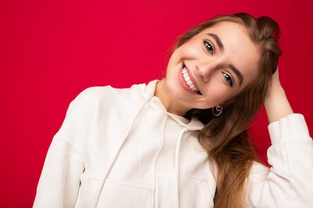 孤立した誠実な感情を持つ若い笑顔の美しいダークブロンドの女性