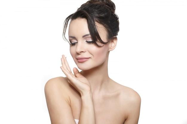 Молодая улыбающаяся красивая девушка наносит крем на щеку