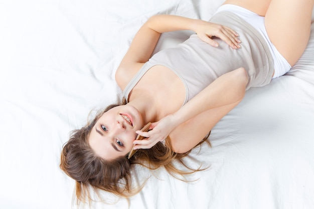 Young smiling beautiful girl in bed with phone at home