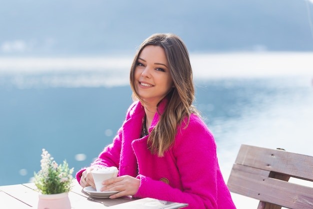 A young, smiling beautiful girl enjoys the beautiful views of the sea. sitting in a street cafe and drinking coffee. alone with nature.