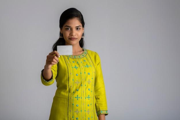 회색 배경에 신용 카드와 함께 포즈 젊은 웃는 아름 다운 소녀.