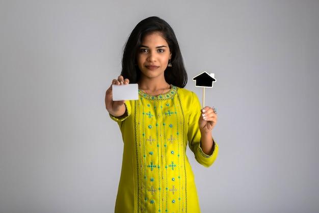 Молодая улыбающаяся красивая девушка показывает кредитную карту или пустую карту с черной доской на сером.