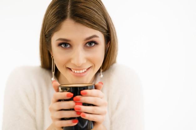 Giovane bella donna felice sorridente con capelli lunghi che gode del cappuccino su priorità bassa bianca. donna di bellezza che gode del caffè. tazza di bevanda calda.