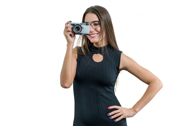 Young smiling beautiful woman in black dress glasses holding photo camera in her hands, taking photo