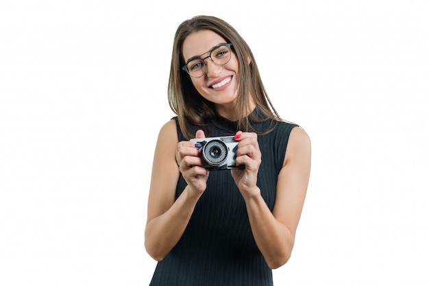 Young smiling beautiful woman in black dress glasses holding photo camera in her hands