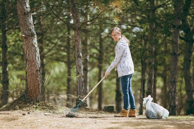Молодая улыбающаяся красивая женщина убирает и использует грабли для сбора мусора возле мешков для мусора в парке или лесу. проблема загрязнения окружающей среды. остановить мусор природы, концепция защиты окружающей среды.