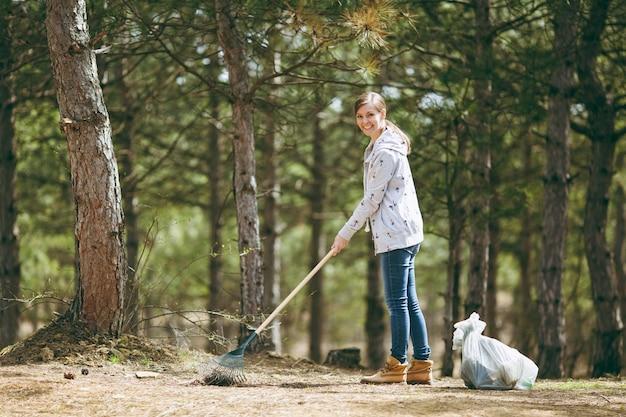 웃고 있는 젊고 아름다운 여성이 공원이나 숲의 쓰레기 봉투 근처에서 쓰레기 수거를 위해 갈퀴를 사용하고 청소합니다. 환경오염 문제