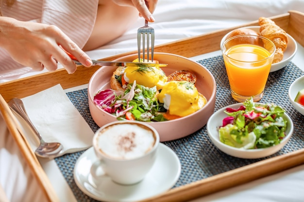 Young smiling beautiful woman having breakfast in bed in cozy hotel room
