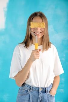 파란색 배경에 고립 된 벽화에 대 한 페인트 롤러를 들고 캐주얼 옷에 젊은 웃는 아름 다운 여자.