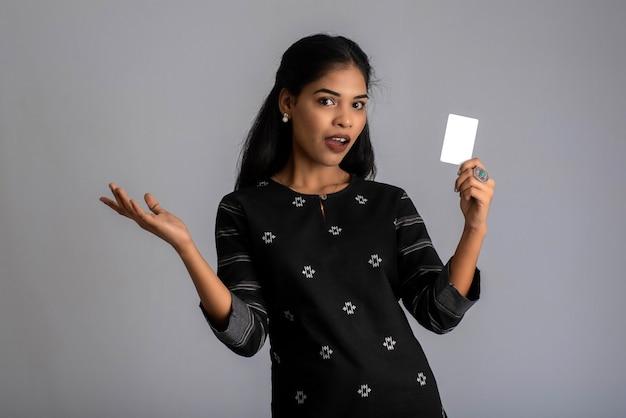 젊은 미소 아름 다운 여자 또는 여자 지불에 대 한 신뢰와 자신감을 보여주는 손에 신용 카드를 제시.