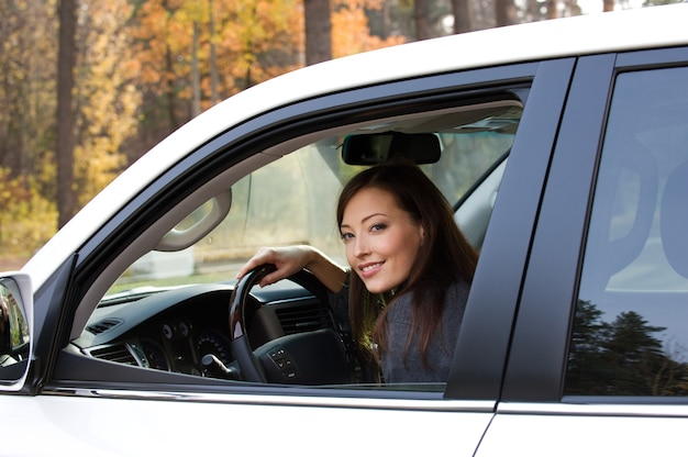 La giovane bella donna sorridente si siede nella nuova automobile
