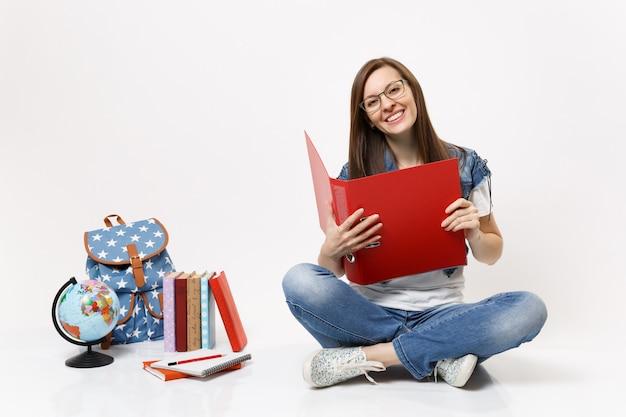 Giovane e bella studentessa sorridente con gli occhiali che tiene in mano una cartella rossa per documenti cartacei seduta vicino allo zaino del globo, libri scolastici isolati