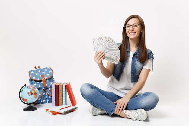 Young smiling beautiful woman student holding bundle lots of dollars, cash money sitting near globe, backpack, school books isolated