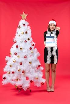 サンタクロースの帽子をかぶって、贈り物を持って誰かを指して飾られたクリスマスツリーの近くに立っている若い笑顔の美しい女性