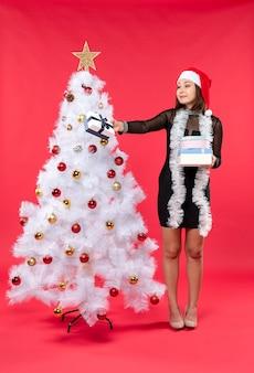 サンタクロースの帽子と贈り物を保持している装飾されたクリスマスツリーの近くに立っている若い笑顔の美しい女性