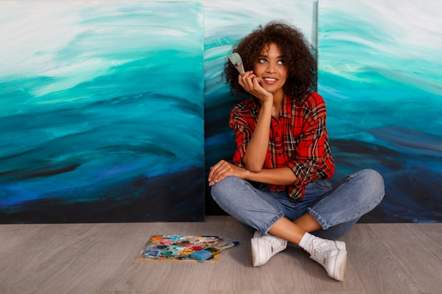 A young smiling black  woman artist in  studio  holding a brush. inspired student   sitting over her artworks.