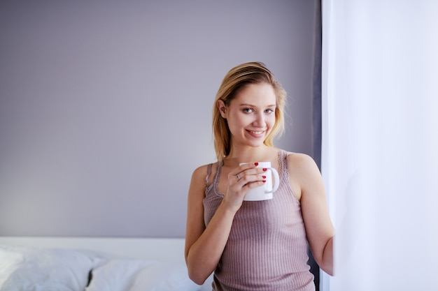 Young smiling blond woman standing next to window and holding mug with fresh morning coffee