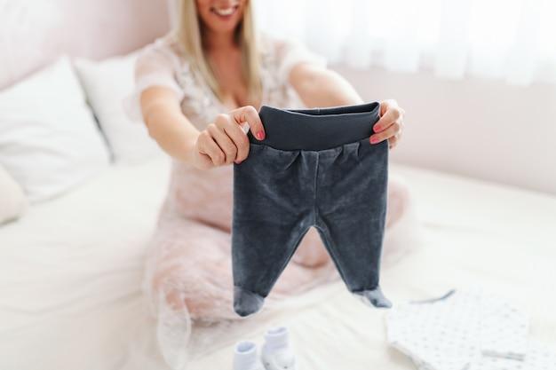 Молодая усмехаясь белокурая кавказская беременная женщина держа брюки младенца пока сидящ на кровати при пересеченные ноги. выборочный фокус на штаны.