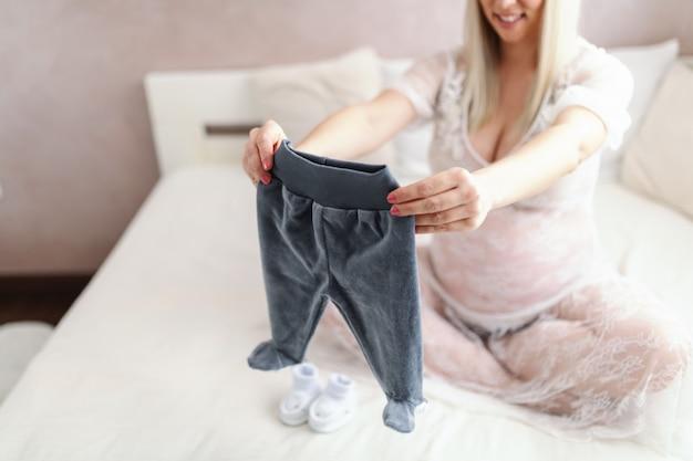 다리와 함께 침대에 앉아있는 동안 아기의 바지를 들고 젊은 웃는 금발 백인 임신 한 여자 넘어. 바지에 선택적 초점.