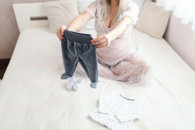 다리와 함께 침대에 앉아있는 동안 아기의 바지를 들고 젊은 웃는 금발 백인 임신 한 여자 넘어.