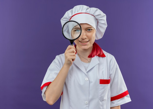 Young smiling blonde female chef in chef uniform looks through magnifying glass or loupe isolated on violet wall