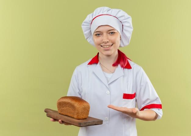 シェフの制服を着た若い笑顔の金髪の女性シェフは、緑の壁に分離されたまな板の上のパンを保持し、指さします