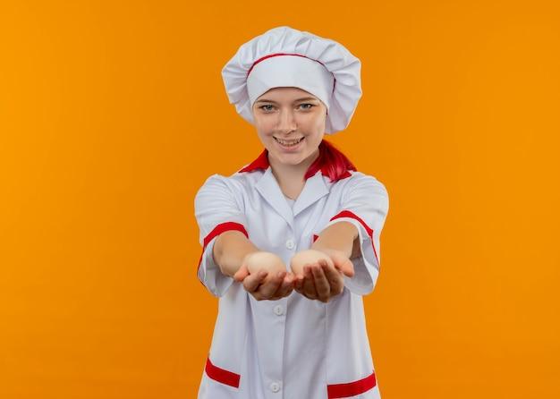 요리사 유니폼에 젊은 미소 금발 여성 요리사는 오렌지 벽에 고립 된 계란을 보유