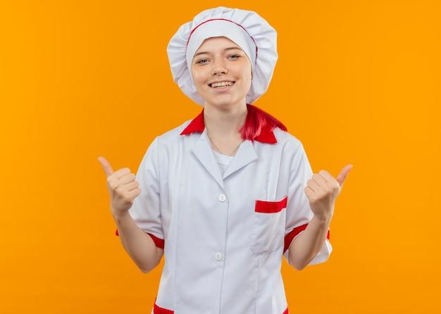 Молодая улыбающаяся блондинка-шеф-повар в униформе шеф-повара показывает палец вверх обеими руками, изолированными на оранжевой стене