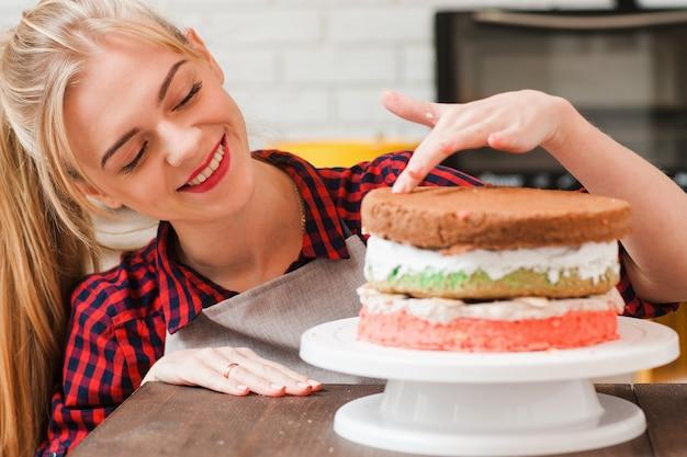젊은 미소 금발 소녀는 부엌에서 나무 테이블에 컬러 비스킷 케이크를 요리