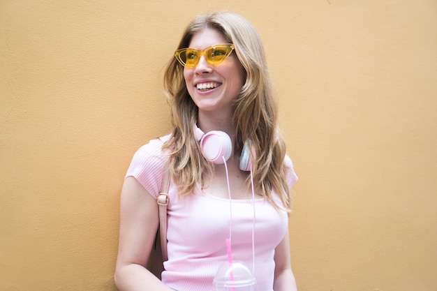 ヘッドフォンと黄色いメガネと若い笑顔のブロンドの女の子