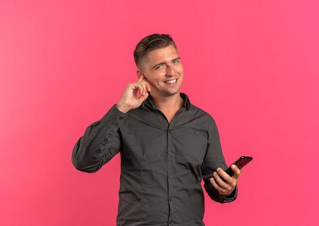 젊은 미소 금발의 잘 생긴 남자는 손가락으로 귀를 닫고 복사 공간이 분홍색 배경에 고립 된 전화를 보유하고